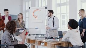 Happy young businessman coach speaking at modern office meeting, leading discussion with team, slow motion RED EPIC. Multiethnic business colleagues listen to stock footage