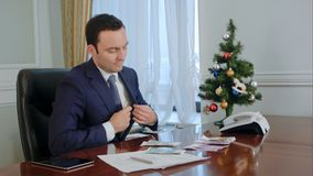 Happy young businessman counts salary near New Year tree in office stock photography