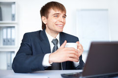 Happy young businessman with cup of coffee Stock Photos