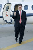 Happy young businessman in front of corporate jet Royalty Free Stock Photography