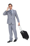 Happy young businessman with his luggage while phoning Stock Images