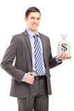 Happy young businessman holding a bag with US dollar sign Stock Photography