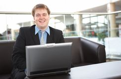 Happy young businessman with laptop Stock Image