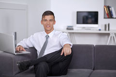 Happy young businessman looking and smiling to us Royalty Free Stock Photography