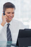Happy young businessman on the phone while working on his tablet. In bright office Stock Images