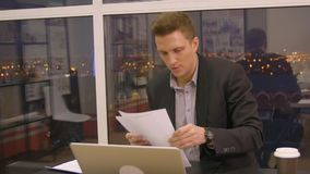 Happy young businessman reading paperwork at desk in office stock footage