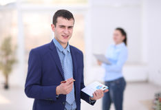 Happy young businessman reading paperwork at in office. Happy young businessman reading paperwork at desk in office Stock Photos