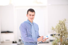 Happy young businessman reading paperwork at in office Royalty Free Stock Photos