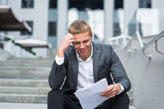 Happy young businessman reading paperwork Royalty Free Stock Photos