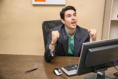 Happy young businessman screaming for joy, at desk Stock Images