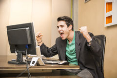 Happy young businessman screaming for joy, sitting at desk. In his office working with computer Royalty Free Stock Photos