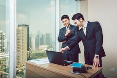 Businessman showing on laptop to his colleague. Happy young businessman showing on laptop to his colleague royalty free stock photo