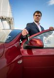 Happy young businessman showing new car keys Stock Photos