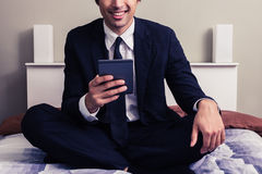 Happy young businessman sitting in bed reading on tablet Royalty Free Stock Images