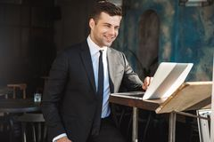Happy young businessman sitting in cafe using laptop computer stock photography