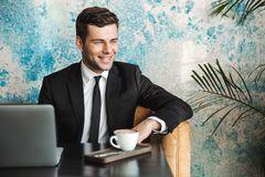 Happy young businessman sitting in cafe using laptop computer stock photo