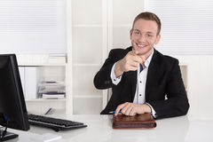Happy young businessman sitting in his office give advice for cu Stock Photo
