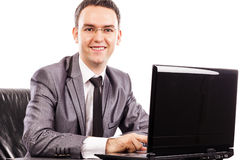 Happy young businessman sitting at office desk working with lapt Royalty Free Stock Image