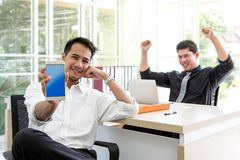 Happy young businessman sitting in the office. Show business succes on mobile phone and computer. stock images