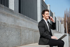 Happy young businessman sitting outdoors talking by phone. Stock Photo