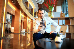 Happy young businessman sitting relaxed on sofa at hotel lobby using smartphone Royalty Free Stock Image