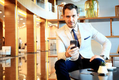Happy young businessman sitting relaxed on sofa at hotel lobby using smartphone Royalty Free Stock Photo