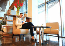 Happy young businessman sitting on sofa in hotel lobby Stock Photo