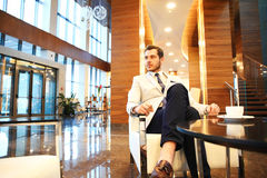 Happy young businessman sitting on sofa in hotel lobby Royalty Free Stock Photography