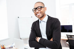 Happy young businessman standing with arms crossed in office Stock Image