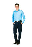 Happy young businessman standing with his hands in pockets on wh Royalty Free Stock Photos