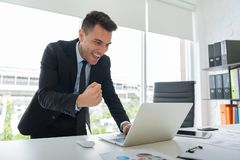 Happy young businessman is standing and looking at laptop. royalty free stock photo