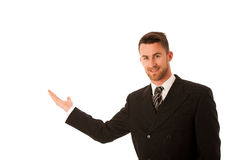 Happy young businessman in suit and tie presenting, promoting, a Royalty Free Stock Image