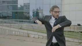 Happy young businessman in suit and tie wearing glasses funny dancing joyfully in nature in front of the corporation -. Happy young businessman in suit and tie stock video