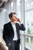 Happy young businessman talking on mobile phone in office Stock Images