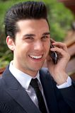 Happy young businessman talking on the phone outdoors. Close up portrait of a happy young businessman talking on the phone outdoors Stock Image