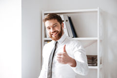 Happy young businessman with thumbs up gesture. Picture of happy young businessman dressed in white shirt standing in office with thumbs up gesture and look at royalty free stock photography