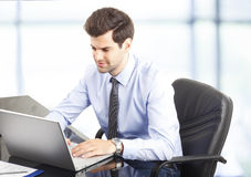 Happy young businessman using laptop in his office royalty free stock photography