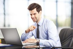 Happy young businessman using laptop in his office Stock Photography