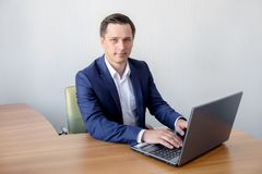 Happy young businessman using laptop at his office desk. Royalty Free Stock Images