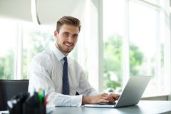 Happy young businessman using laptop at his office desk Stock Image