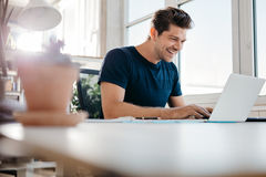 Happy young businessman using laptop at his office desk Royalty Free Stock Photos