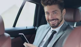 Happy young businessman using mobile phone in back seat of car Royalty Free Stock Photos