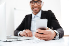 Happy young businessman using mobile phone while working Stock Images