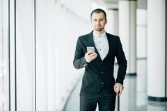Happy young businessman walking and looking at mobile phone at airport. Handsome business executive texting on smartphone while wa royalty free stock photos