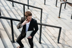 Happy young businessman walking outdoors. Stock Photos