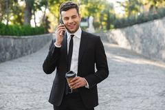 Happy young businessman walking outdoors near business center talking by mobile phone drinking coffee royalty free stock images