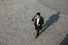 Happy young businessman walking outdoors Stock Photo