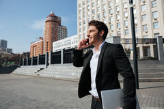 Happy young businessman walking outdoors talking by phone. Royalty Free Stock Photography