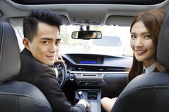 Happy young businessman and woman driving in the car Royalty Free Stock Photography