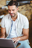 Happy young businessman working at laptop drinking coffee. At coffee Stock Photography